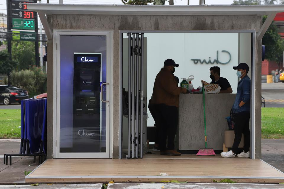Government employees open the customer service area of a Chivo digital wallet machine, which exchanges cash for Bitcoin, at Las Americas Square in San Salvador.