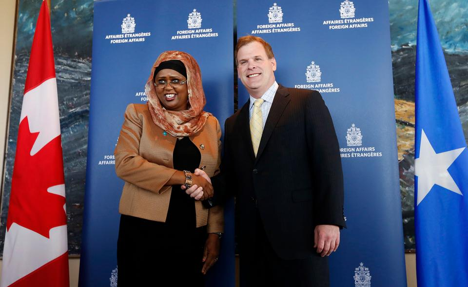 Fawzia Yusuf Adam shakes hands with her the then Canadian counterpart John Baird in October 1, 2013 (Reuters)