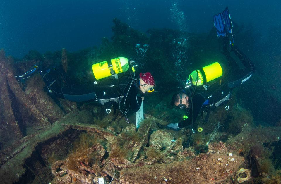 Divers exploring the submerged battleship HMS Majestic.