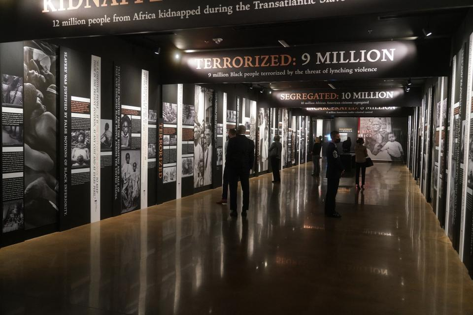 Image courtesy of the Equal Justice Initiative, shows people looking at an exhibit at the Legacy Museum (AFP)