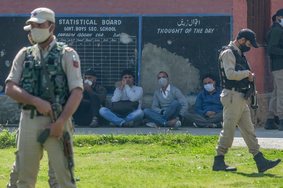 Indian paramilitary soldiers stand guard next to a group of teachers sitting inside a government school where two teachers were shot dead by assailants in the outskirts of Srinagar, Indian controlled Kashmir, Thursday, Oct. 7, 2021.