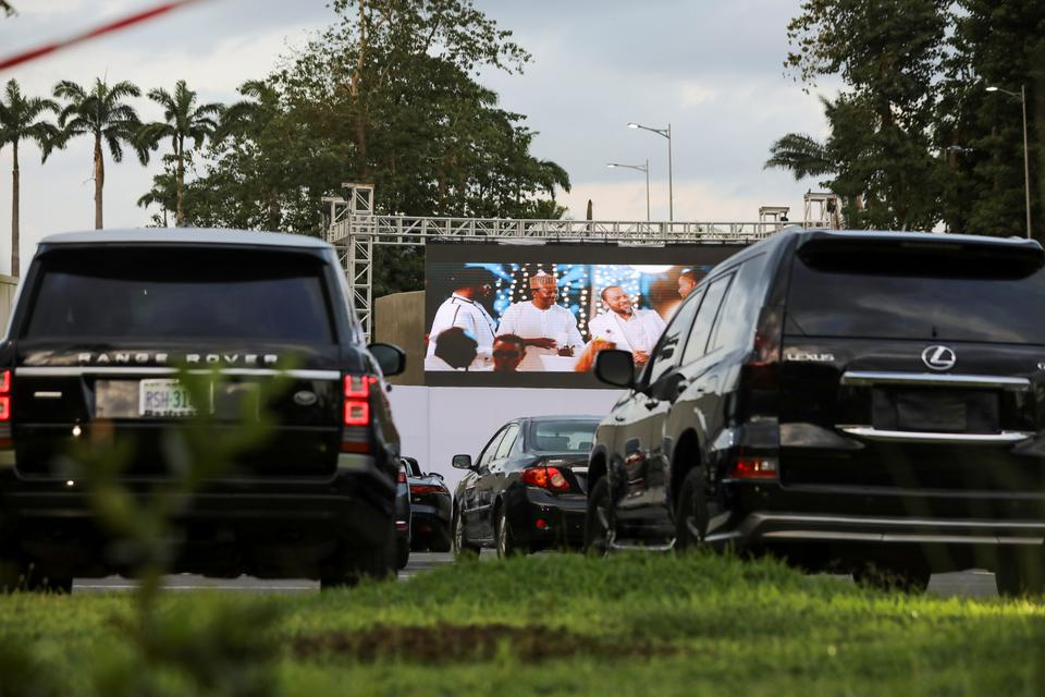 Movie audiences sit in their parked cars as they watch a movie at a drive-in cinema, following the relaxation of lockdown, amid the coronavirus disease (COVID-19) outbreak in Abuja, Nigeria May 20, 2020.