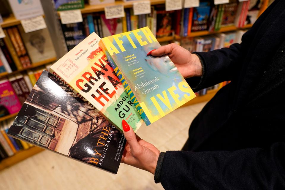 A member of staff holds copies of books by Zanzibar-born novelist Abdulrazak Gurnah in a book shop in London on October 7, 2021.