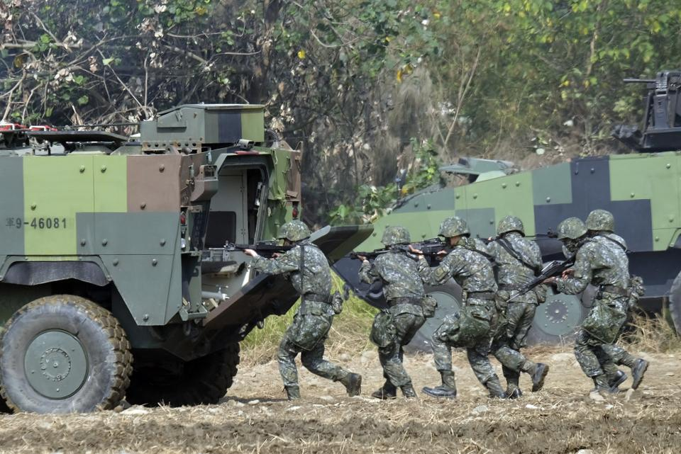 Taiwan special forces personnel walk behind an armoured personnel carrier during an annual military drill in Taichung, central Taiwan, January 17, 2017