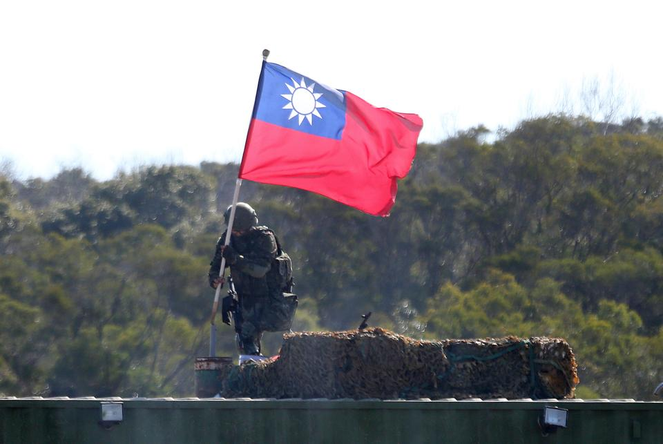 A soldier holds a Taiwan national flag during a military exercise in Hsinchu County, northern Taiwan, Tuesday, Jan. 19, 2021.