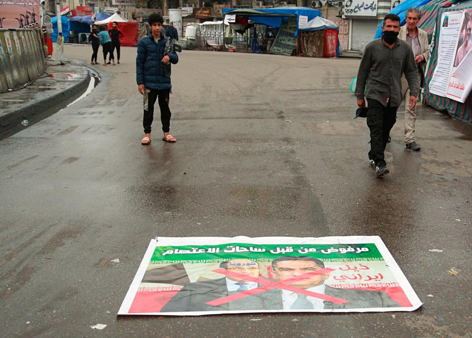 Anti-government protesters pass by a defaced poster with pictures of former Prime Minister Nouri al-Maliki, left, and Prime Minister-designate Adnan Al-Zurfi with Arabic text reading