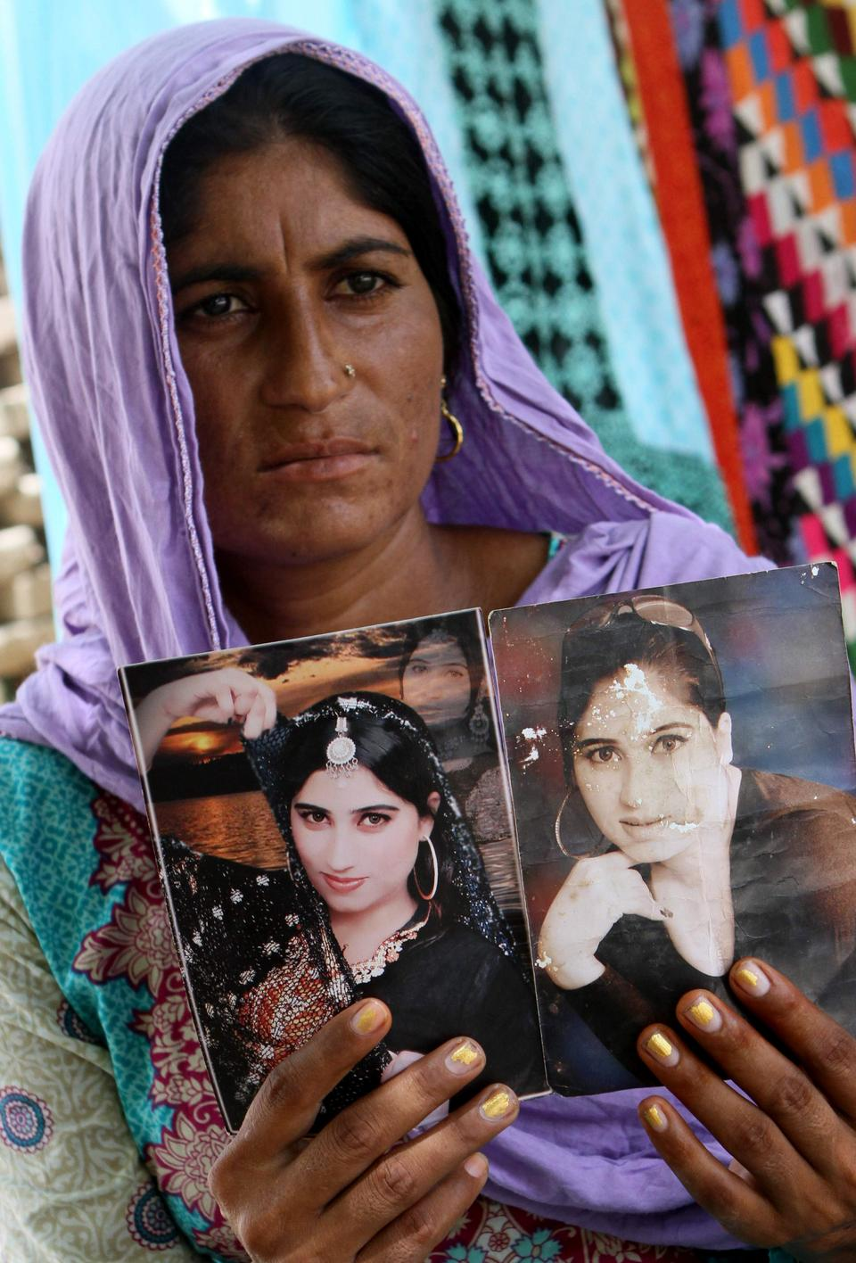 In this October 18, 2016, photo, a family member shows pictures of controversial social media celebrity Qandeel Baloch, in Shah Sadderuddin, Pakistan. Baloch grew up in a poor farming family but