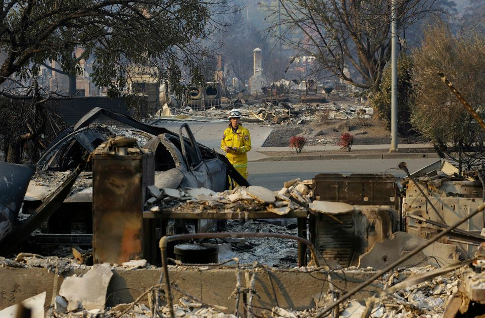 An official from Cal Fire department inspects damage at homes destroyed by fires in Santa Rosa, California, Thursday, Oct. 12, 2017.