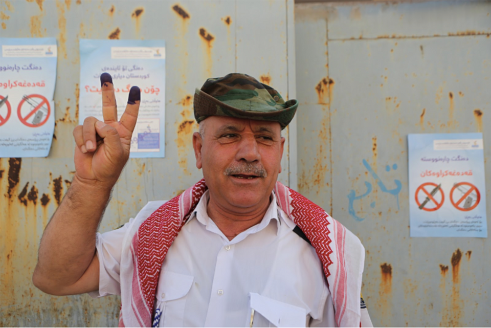 An Iraqi Kurdish man poses with his inked fingers after casting a vote during a referendum on independence from Iraq in Erbil, Iraq, Monday, Sept. 25, 2017.