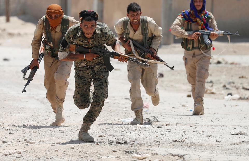 YPG militants run across a street in Raqqa, Syria July 3, 2017.