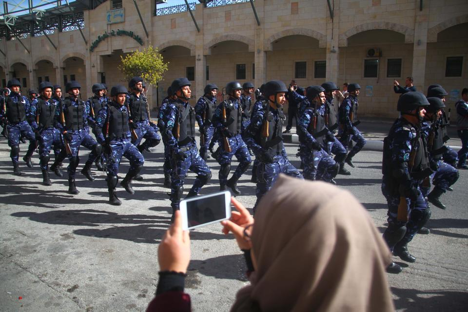 A woman takes photos of soldiers marching during a parade marking the 29th anniversary of Palestinian Declaration of Independence in Hebron, West Bank on November 14, 2017.