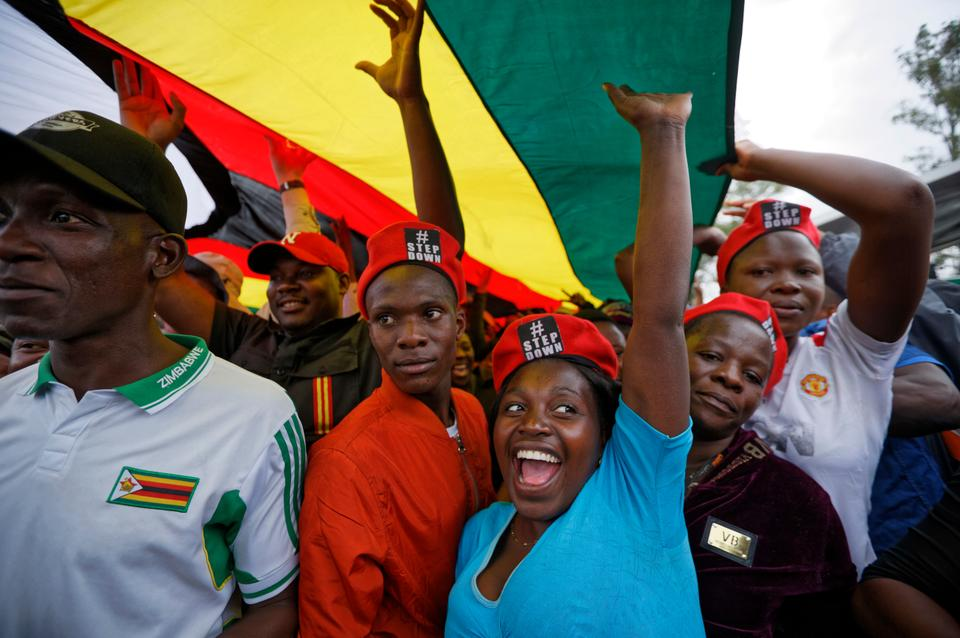 Protesters raise their fists under a large national flag, at a demonstration of tens of thousands in Harare last Saturday.