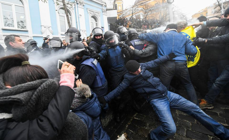 Police officers (C) use pepper spray during clashes with supporters of former Georgian president attempting to block a police van in which he is transported after being arrested, in downtown Kiev.