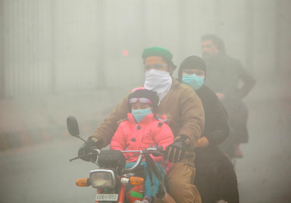 People use face masks to protect themselves from morning smog as they ride on bike along a road in Lahore, Pakistan November 10, 2017.