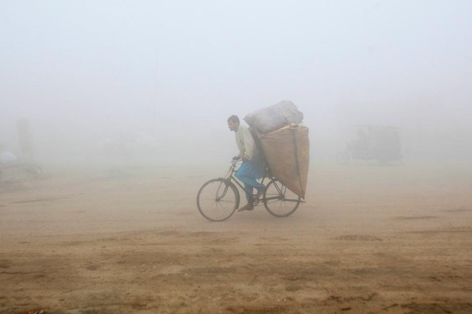 A man rides A bicycle carrying sacks of recyclables amid morning smog in Lahore, Pakistan November 10, 2017.