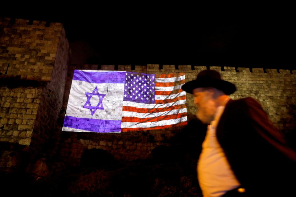 A man walks by as the Israeli national flag and an American one are projected on a part of the walls surrounding Jerusalem's Old City, on December 6, 2017.