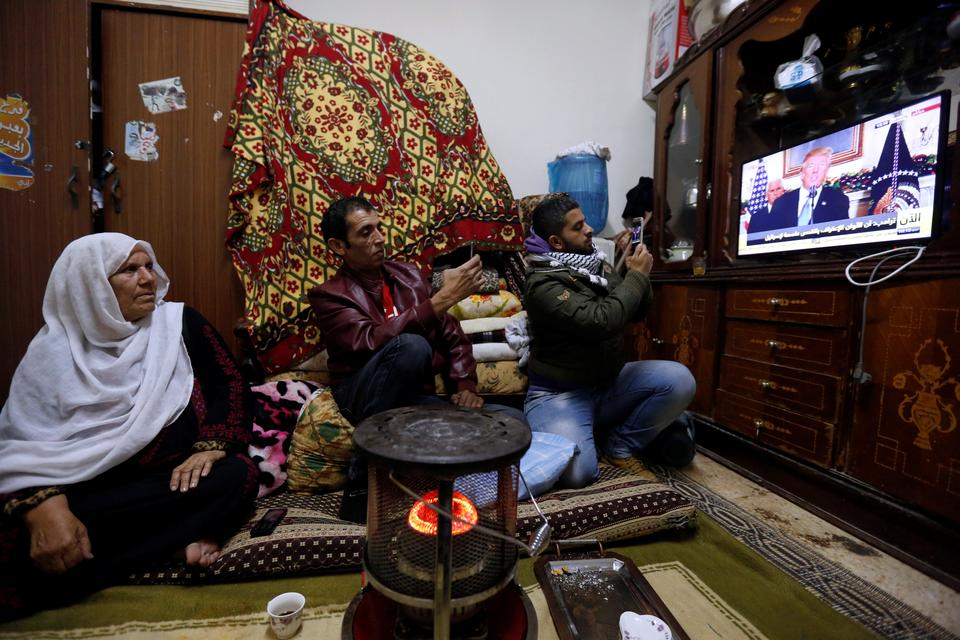 His televised announcement was followed closely all around the world. In this picture, a Palestinian refugee family  living in Al Baqaa Palestinian refugee camp, in Jordan's Amman watches the broadcast.