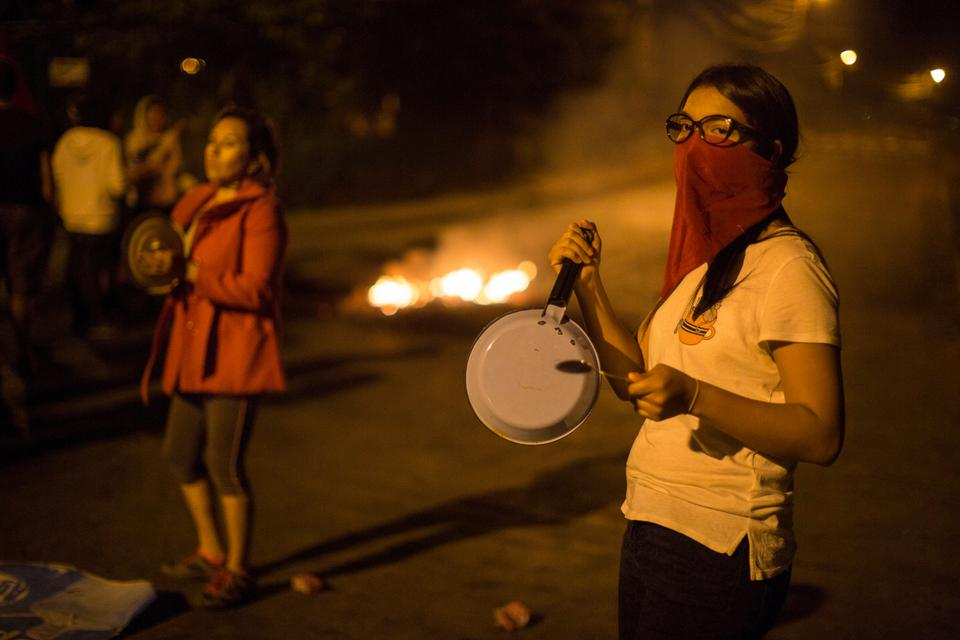 Anti-government demonstrators bang cooking pots in protest during a government-imposed dawn-to-dusk curfew in Tegucigalpa, Honduras, Sunday, December 3, 2017
