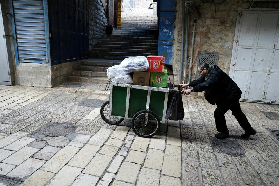 A man pushes a cart past closed shops in Jerusalem's Old City after Palestinian  factions called a general strike to protest US President Donald Trump's announcement that he has recognised the city as Israel's capital.