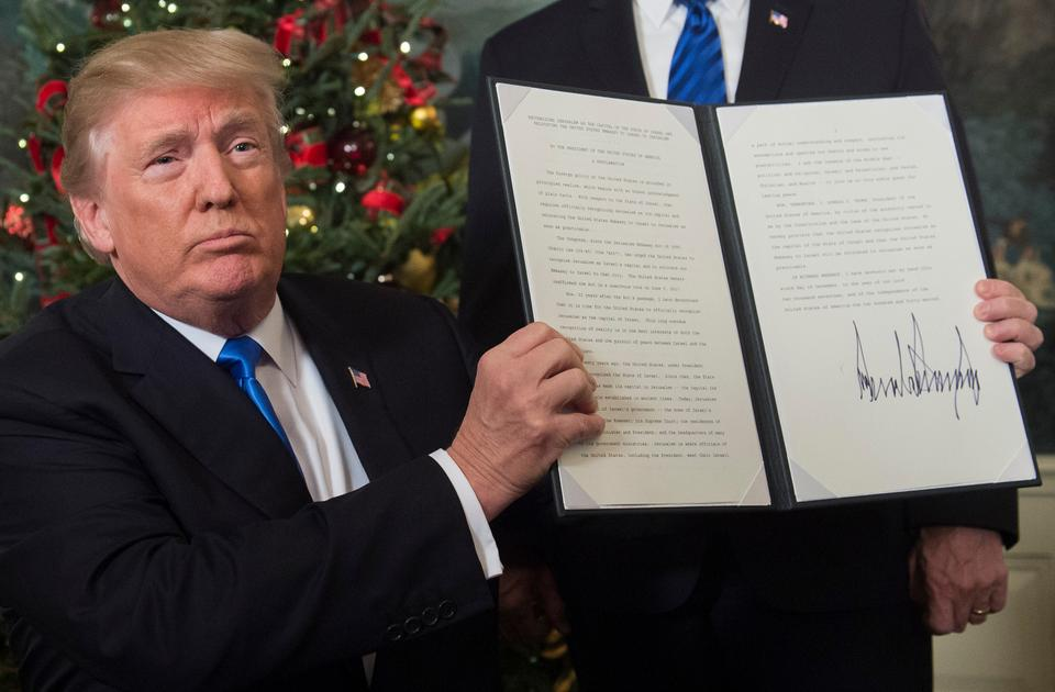 US President Donald Trump holds up a signed memorandum after he delivered a statement on Jerusalem from the Diplomatic Reception Room of the White House in Washington, DC on December 6, 2017.
