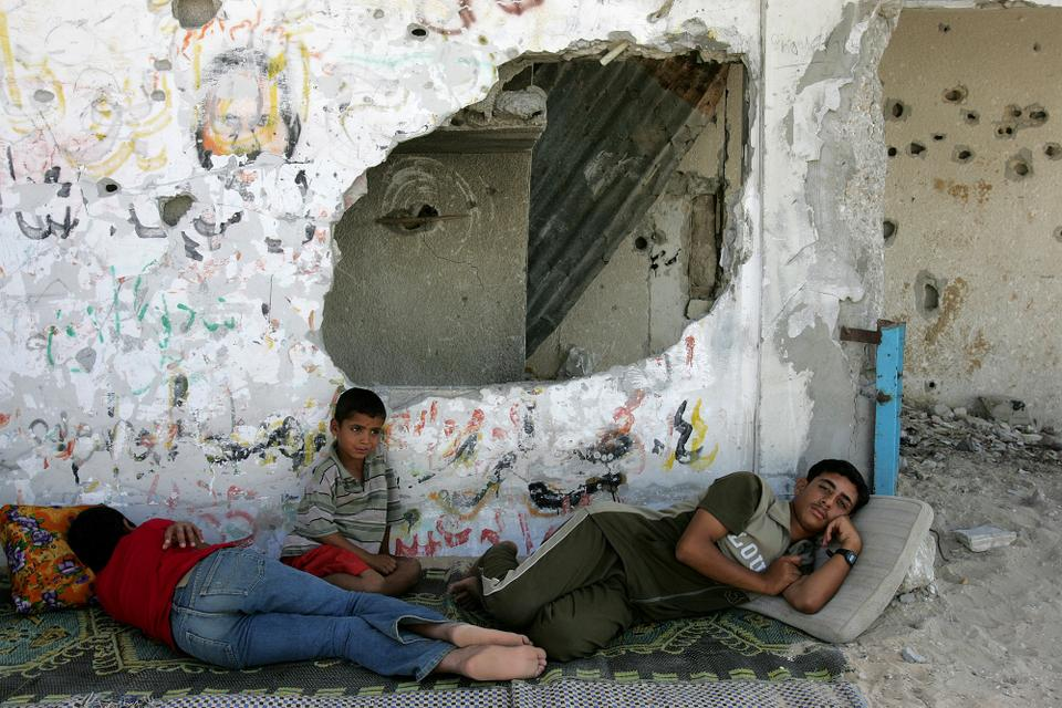 Young Palestinians rest in the shade of a building destroyed during the second intifada in 2005.