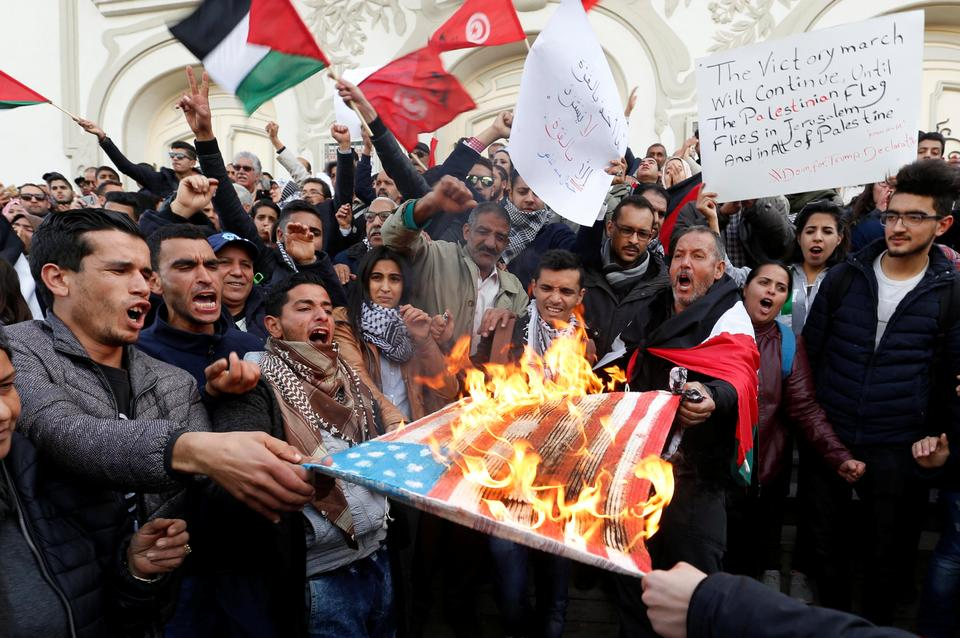 Protesters burns a U.S. flag during a protest against Trump's decision to recognise Jerusalem as the capital of Israel, in Tunis, Tunisia, on December 7, 2017.