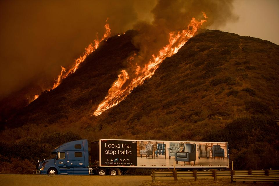Flames are seen from the Thomas fire burn above a truck on Highway 101 north of Ventura, California.The wind-swept blazes have forced tens of thousands of evacuations and destroyed dozens of homes.
