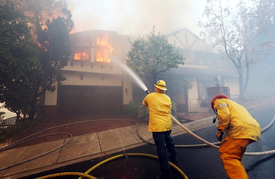 Los Angeles firefighters battle to contain flames to a burning home and prevent the fire's spread to adjoining properties in the Bel Air district of Los Angeles on Wednesday, December 6, 2017.
