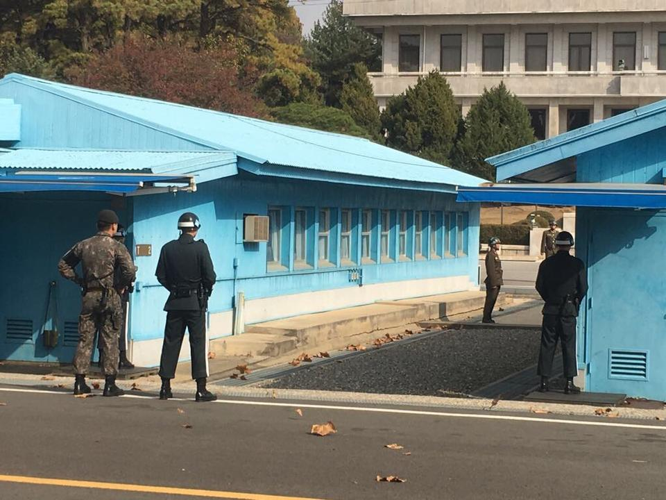 Three blue huts, where the Korean Armistice Agreement was signed in 1953, sit astride the line that separates North from South Korea, with soldiers from both sides staring at each other.