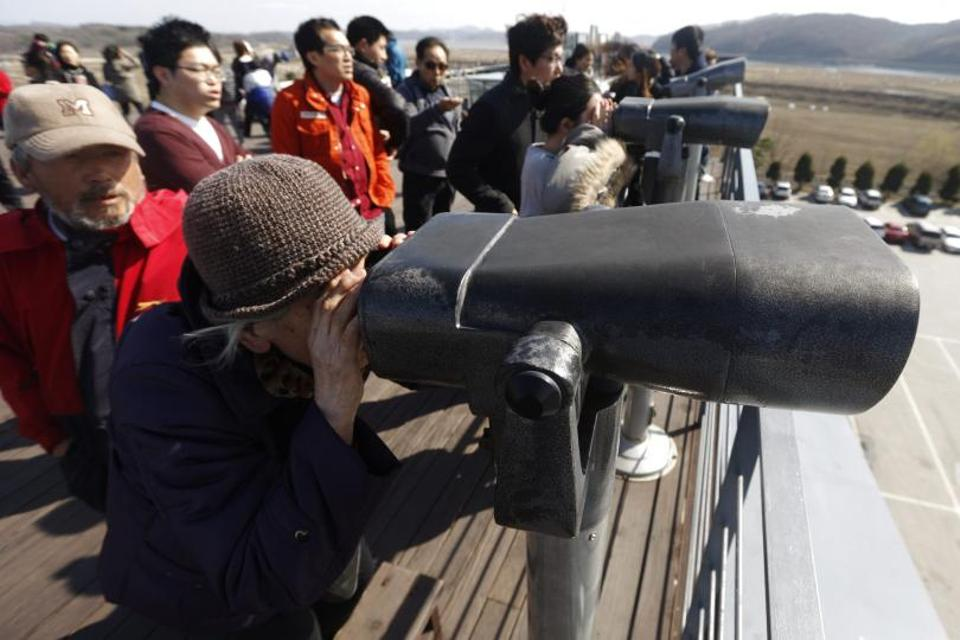 South Koreans look north through binoculars near the demilitarised zone, a line that separates North Korea from South Korea in Paju.