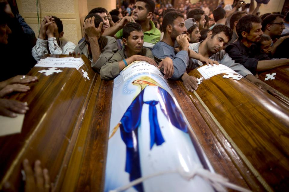 Relatives of the victims surround their coffins, during a funeral service, at Abu Garnous Cathedral in Minya, Egypt.