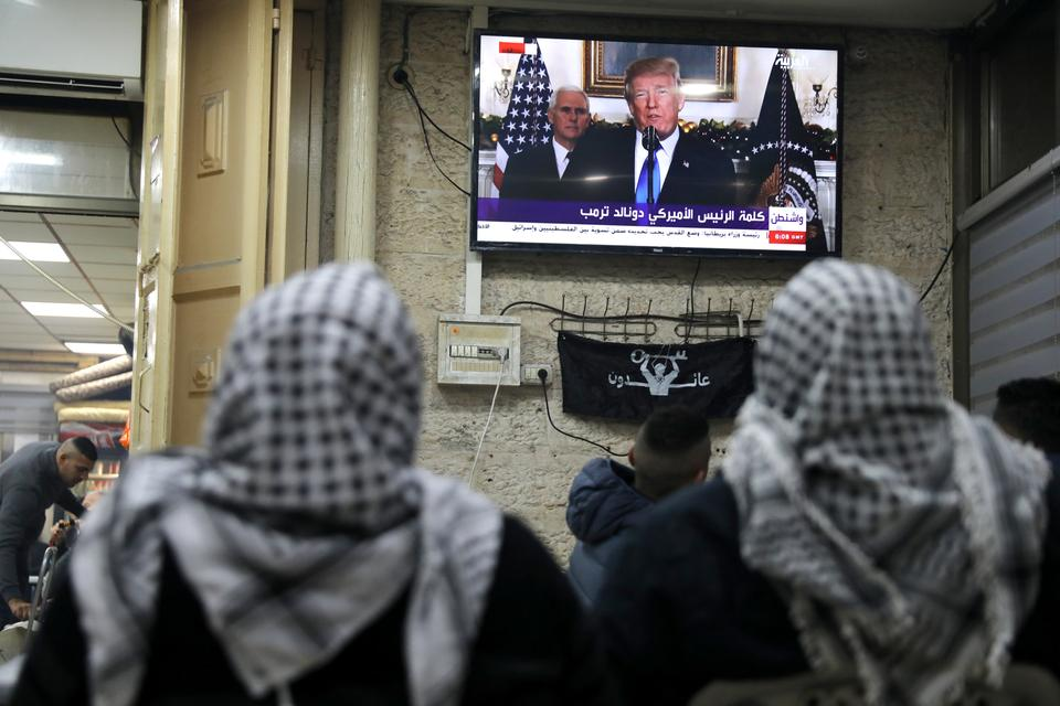 Palestinians in Jerusalem's Old City watch a televised broadcast of US President Donald Trump announcing US recognition of Jerusalem as the capital of Israel.