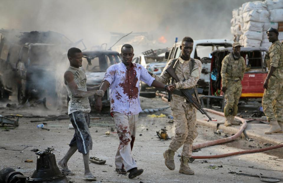 A Somali soldier helps a civilian who was wounded in the blast in Mogadishu, Somalia.