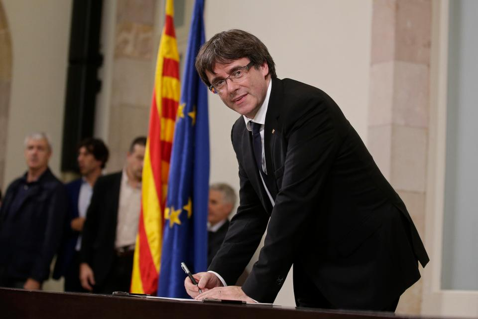 Catalan President Carles Puigdemont signs an independence declaration document after a parliamentary session in Barcelona, Spain.
