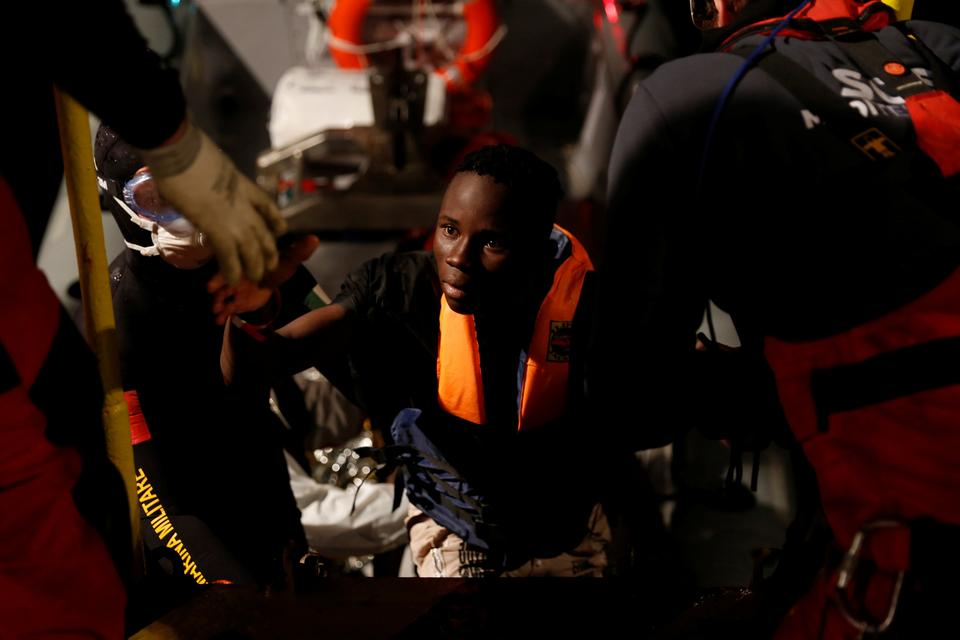 A migrant rescued from a rubber dinghy is helped aboard the MV Aquarius, a search and rescue ship run in partnership between SOS Mediterranee and Medecins Sans Frontieres, in the central Mediterranean, off the coast of Libya, December 15, 2017.