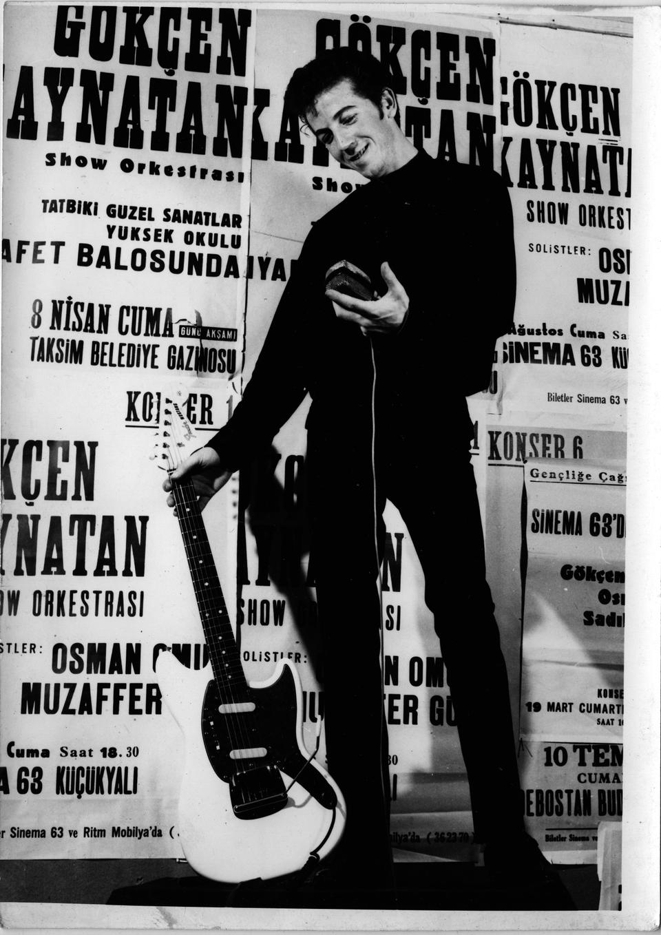 In a photo from 1960, Gokcen Kaynatan, then a 21-year-old student, poses with his guitar in front of posters announcing an April concert at the ball for Tatbiki Guzel Sanatlar Yuksek Okulu—today's Marmara University Faculty of Fine Arts—students, the university he attended for Interior Architecture and Industrial Design.