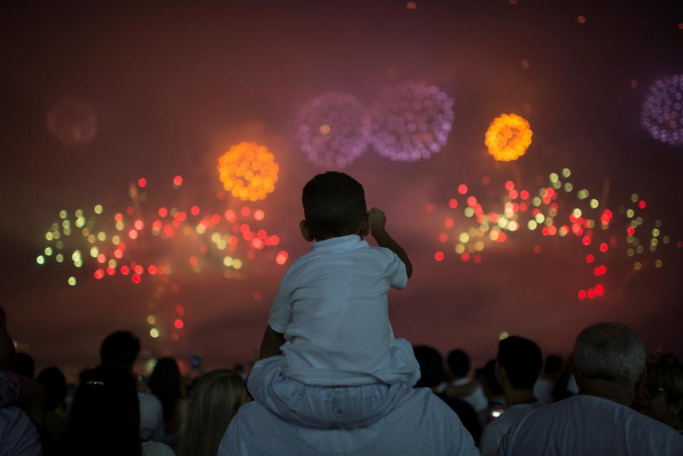 People watch as fireworks explode over Copacabana beach during New Year celebrations in Rio de Janeiro, Brazil.