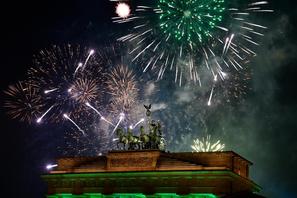Fireworks explode behind the quadriga of Berlin's landmark the Brandenburg Gate to usher in the New Year.