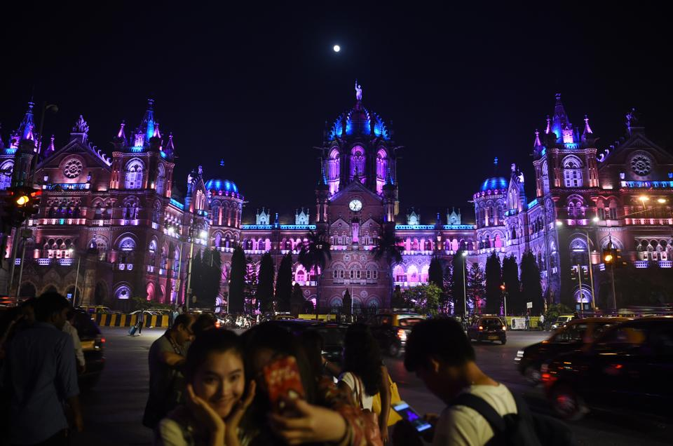 Indians take pictures in front of the lit up Chattrapathi Shivaji Terminus (CST) railway station ahead of New Year's eve celebrations in Mumbai.