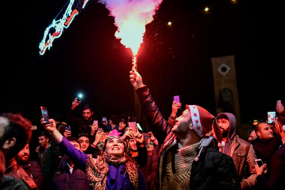People gather to celebrate New Years in Istanbul, Turkey, a year after a gunman killed 39 people in Reina night club.