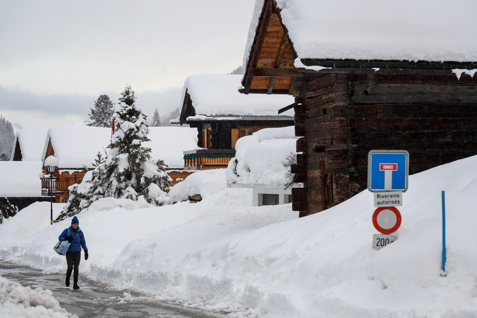 A pedestrian walks in the small resort of Zinal, Swiss Alps on January 9, 2018, after the access road cut by heavy snowfall reopened.