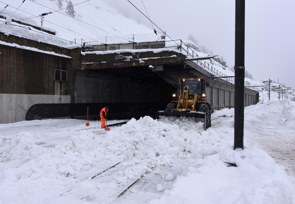 Workers clear snow from a train tunnel in Zermatt on January 9, 2018 after heavy snowfall and avalanches trapped more than 13,000 tourists at Zermatt, one of Switzerland's most popular ski stations.