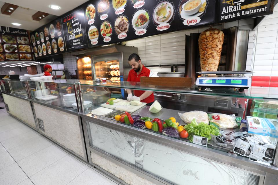 Hani, who is a Syrian working for a kebab shop, is making preparations for the busy lunch time in Istanbul's Fatih district on January 11, 2018.