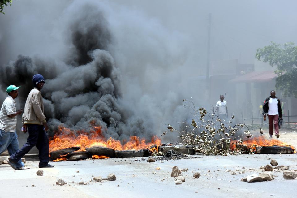 Resident of Lusaka's Kanyama Township walk past a burning barricade of tyres, Zambia, January 12, 2018.