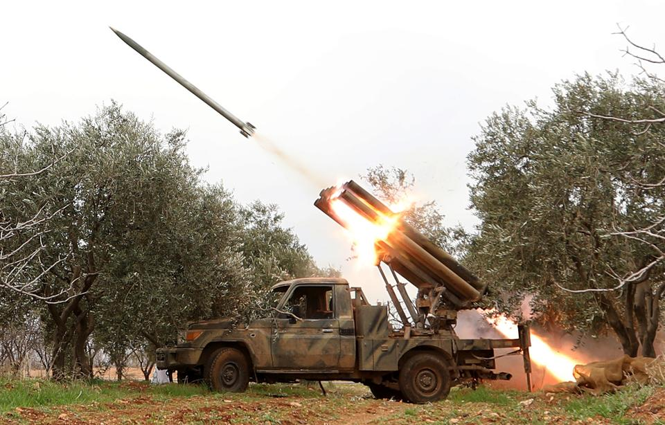 Hayat Tahrir al-Sham militants fire missiles from a village near al-Tamanah during ongoing battles with regime forces in Syria's Idlib province on January 11, 2018.
