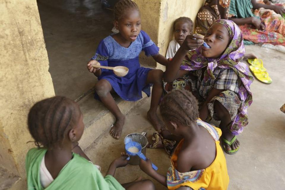 Children rescued by Nigerian soldiers from Boko Haram eat food at a refugee camp in Yola, Nigeria May 4, 2015.