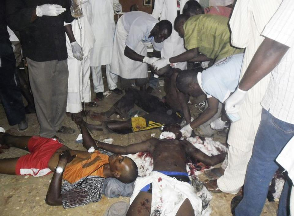 Medical staff attends the people injured in a bomb after a girl suicide bomber as young as 10 blew herself up at a busy market, north-eastern Nigeria.