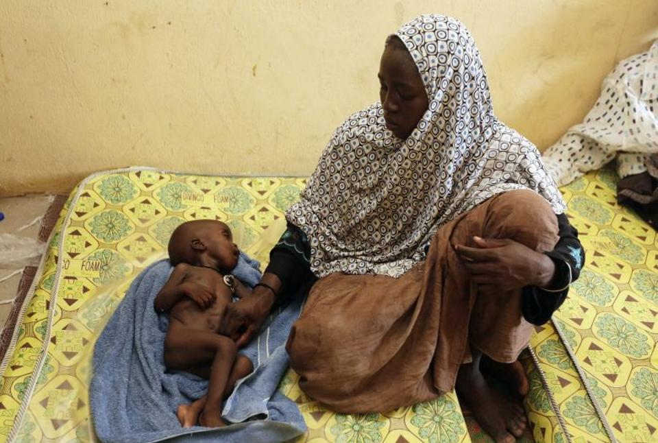 A women rescued by Nigerian soldiers from Boko Haram looks at her malnourished child at a refugee camp in Yola, Nigeria on May 4, 2015.