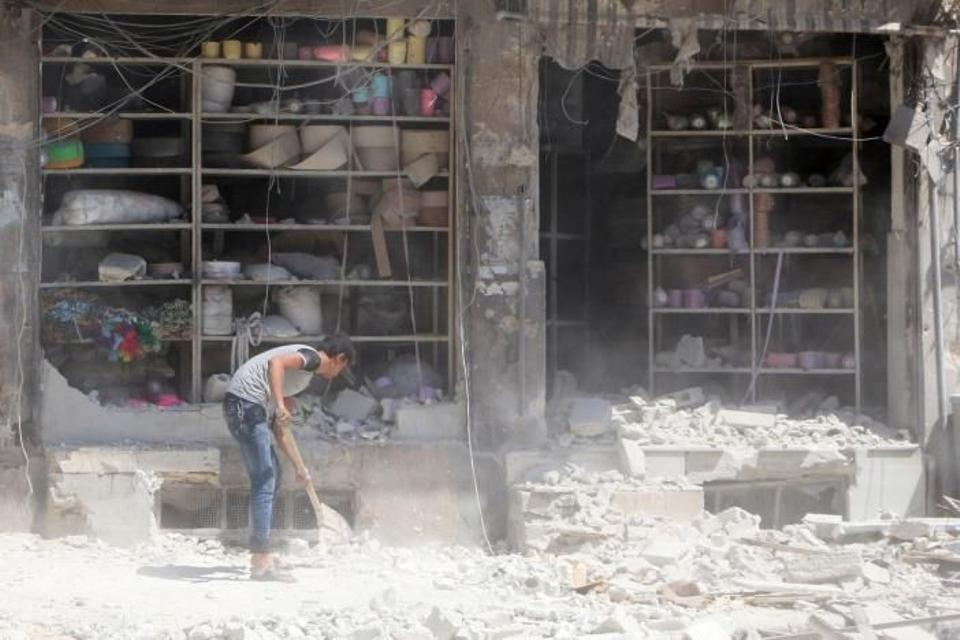 A civilian removes the rubble in front of a damaged shop after an airstrike in the rebel held al-Saleheen neighborhood of Aleppo.