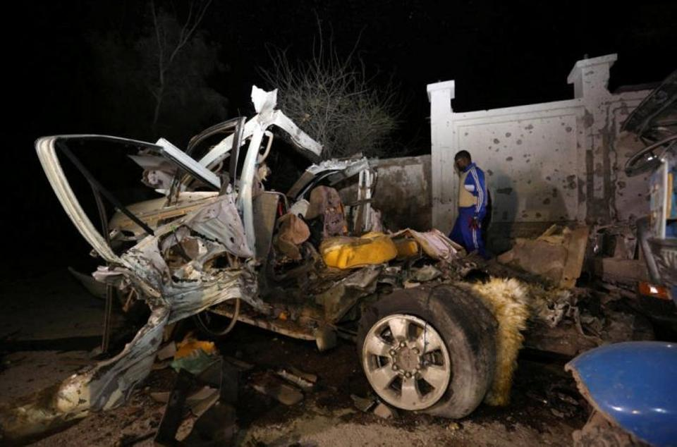 A Somali policeman looks at the wreckage of a vehicle destroyed in a car bomb explosion at the Banadir beach restaurant on August 25, 2016.